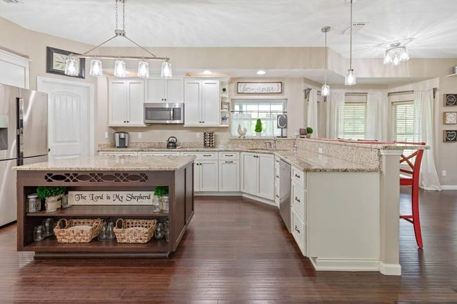 The chef's kitchen is equipped with granite countertops, soft-close drawers, stainless-steel appliances, a cooktop, double oven and a large island.
