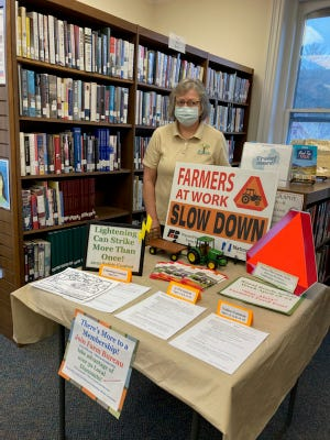 """Women's Leadership Chair, Bonnie LaTourette with a Rural Roads Safety display in the Wayne County Public Library.  Drivers should be cautious when they see a """"Farmers at Work"""" sign or a Slow-Moving Vehicle emblem."""