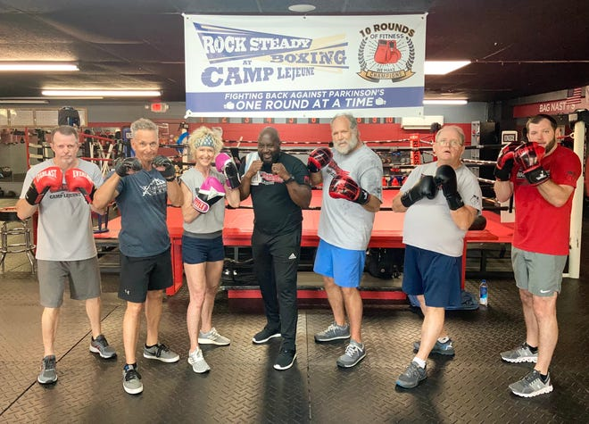 From left: Jimmy Pierce, Brad Lindberg, Amy Lindberg, Coach Emanuel Simmons, Bill Foster, Cameron Brooks and Barrett Foster pose for a photo after a Rock Steady Boxing workout at 10 Rounds of Fitness in Jacksonville, Monday, May 17, 2021.