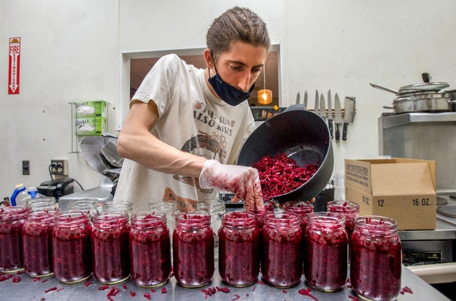 Joe Zich, owner of 309 Cultures, stuffs jars with a pound each of Purple Kurry Kraut, his homemade brand of sauerkraut he creates in the kitchen at Sunrise Health Foods in the Metro Centre in Peoria.