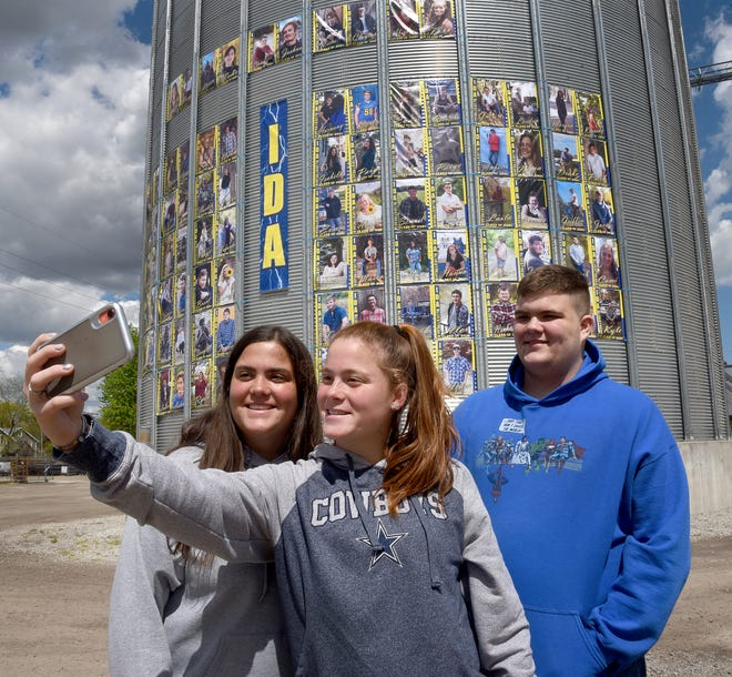 Hanna Muir takes a selfie with sister Ava and brother Kennan in front of the Ida Farmer Co-op grain elevators, which feature posters of the 98 students graduating from Ida High School. The triplets are among the graduating class this year.