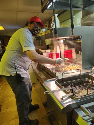 Jon Christy, nephew of the owner, scoops up french fries in the concession stand at the Sundance Drive-In Theatre in Oregon, Ohio.