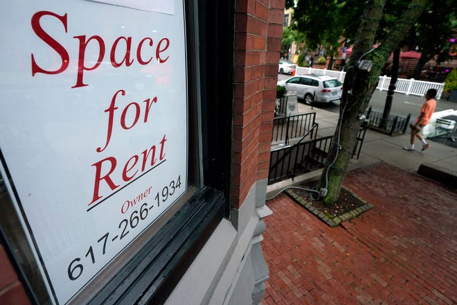 A passerby walks past a business storefront with a space for rent sign in a window in Boston. [AP File Photo/Steven Senne]