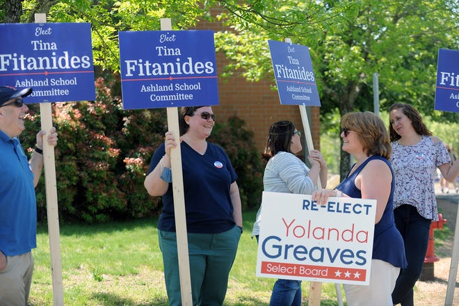 Ashland School Committee candidate Tina Fitanides, second from left, and Select Board candidate Yolanda Greaves speak outside the Ashland High School polling place on Tuesday during the annual town election.