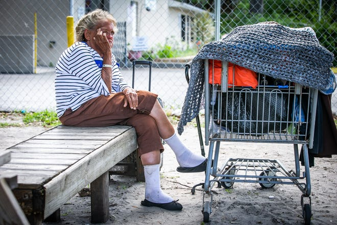 """""""This is my sofa and my bed. I need a mat, because these boards are hard,"""" Carol Stark said Tuesday about the bench she sleeps on at Interfaith Emergency Services' open-air shelter. """"This is my closet,"""" Stark said about her shopping cart with all of her belongings."""