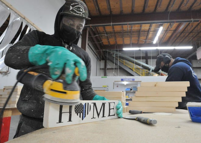 Woodcrafter Robenson St. Hillien sands the edges of a sign in the woodworking shop at the Rustic Marlin in Hanover, Wednesday, May 12, 2021.