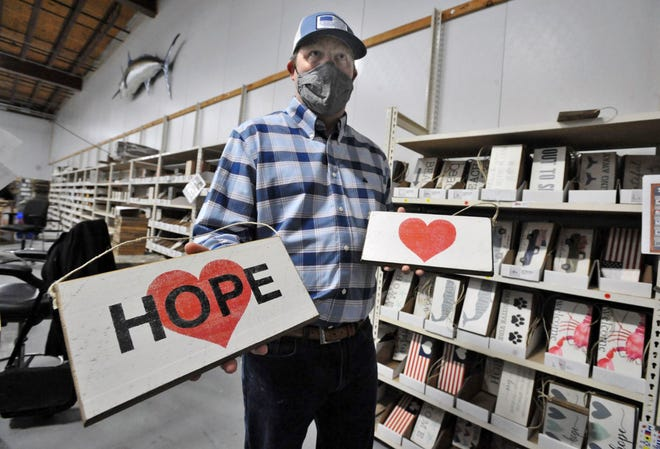 """Rustic Marlin of Hanover co-owner Brian O'Neil holds the """"signs of hope"""" where proceeds from the sales are donated to small businesses impacted by the COVID-19 pandemic, Wednesday, May 12, 2021."""
