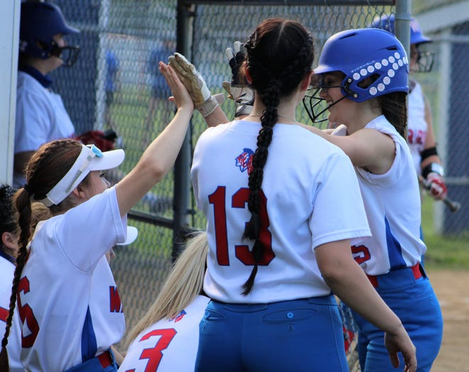 Winnacunnet's Kate Gagne is congratulated by teammates after scoring a run during a five-run third inning in Monday's Division I softball game against Portsmouth.