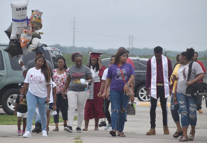 Graduates and family members converge outside as they await their turn to receives their diploma at White Castle High School, which was the first of the Iberville Parish schools to host commencement ceremonies adjuasted for the COVID-19 pandemic.