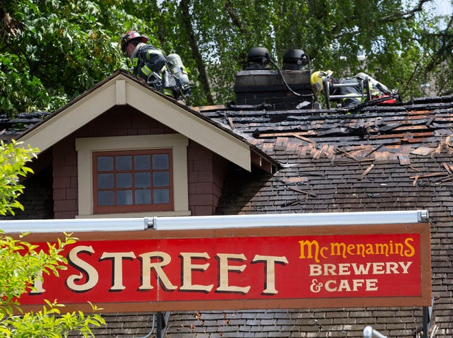 Eugene Springfield firefighters pull off the roof of McMenamins High Street Brewery & Café on High Street in Eugene in search of hotspots after a fire in the rafters of the business.