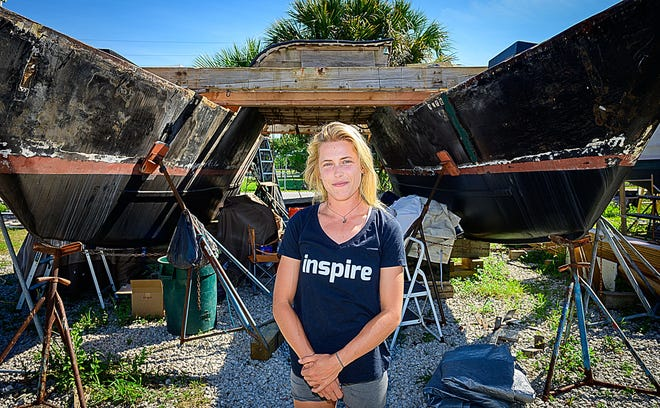 Kiana Weltzien stands in front of her 41-foot catamaran that she is repairing in a boatyard on Riberia Street in St. Augustine on Tuesday. Weltzien sailed worldwide and lived on the boat for the last two years. She plans to sail to Europe at the end of this month.