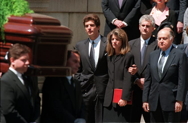 John F. Kennedy Jr., puts his arm around his sister, Caroline Kennedy Schlossberg, as the casket bearing the remains of their mother, former first lady Jacqueline Kennedy Onassis, is carried from St. Ignatius Loyola Roman Catholic Church following a funeral mass in New York City on May 23, 1994. Caroline's husband, Edwin Schlossberg, is second from right. Mrs. Onassis' longtime friend, Maurice Tempelsman, is at far right.