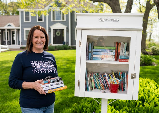 Rutland resident Amy Benoit poses with her Little Free Library outside her home Tuesday.