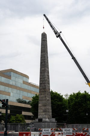 Construction workers begin the process of removing the Vance Monument on Tuesday, May 18, 2021.