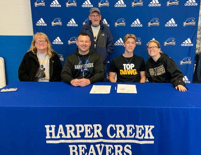 Joined by family and coaches, Harper Creek's Bailey Bush commits to play football and run track at Adrian College at a signing ceremony at Harper Creek High School on Monday.