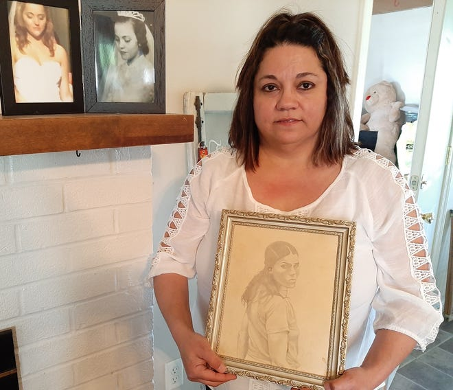 Anna Garcia displays a portrait of her mother with wedding photos of her mom and her oldest daughter on her mantle.