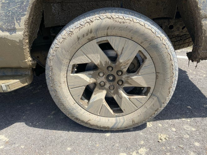 Aerodynamic 22-inch wheel on 2022 Ford F-150 Lightning electric pickup, caked in mud after off roading.