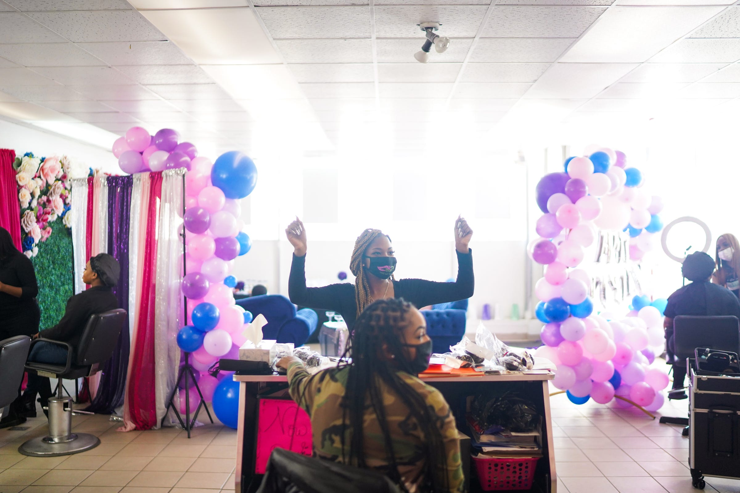 """Tia Russell throws her hands up as the music comes back on during the fourth annual Self-Awareness Appreciation Day put on by the non-profit, Take My Hand at the ShayBaby Make Up Bar on Sunday, March 21, 2021 in Warren. Take My Hand has been steadily growing the event each year. """"The first year we had four people. That's it,"""" she said. The event brought together 11 volunteer hairdressers, make-up artists, nail techs and a barber to serve 20 people."""