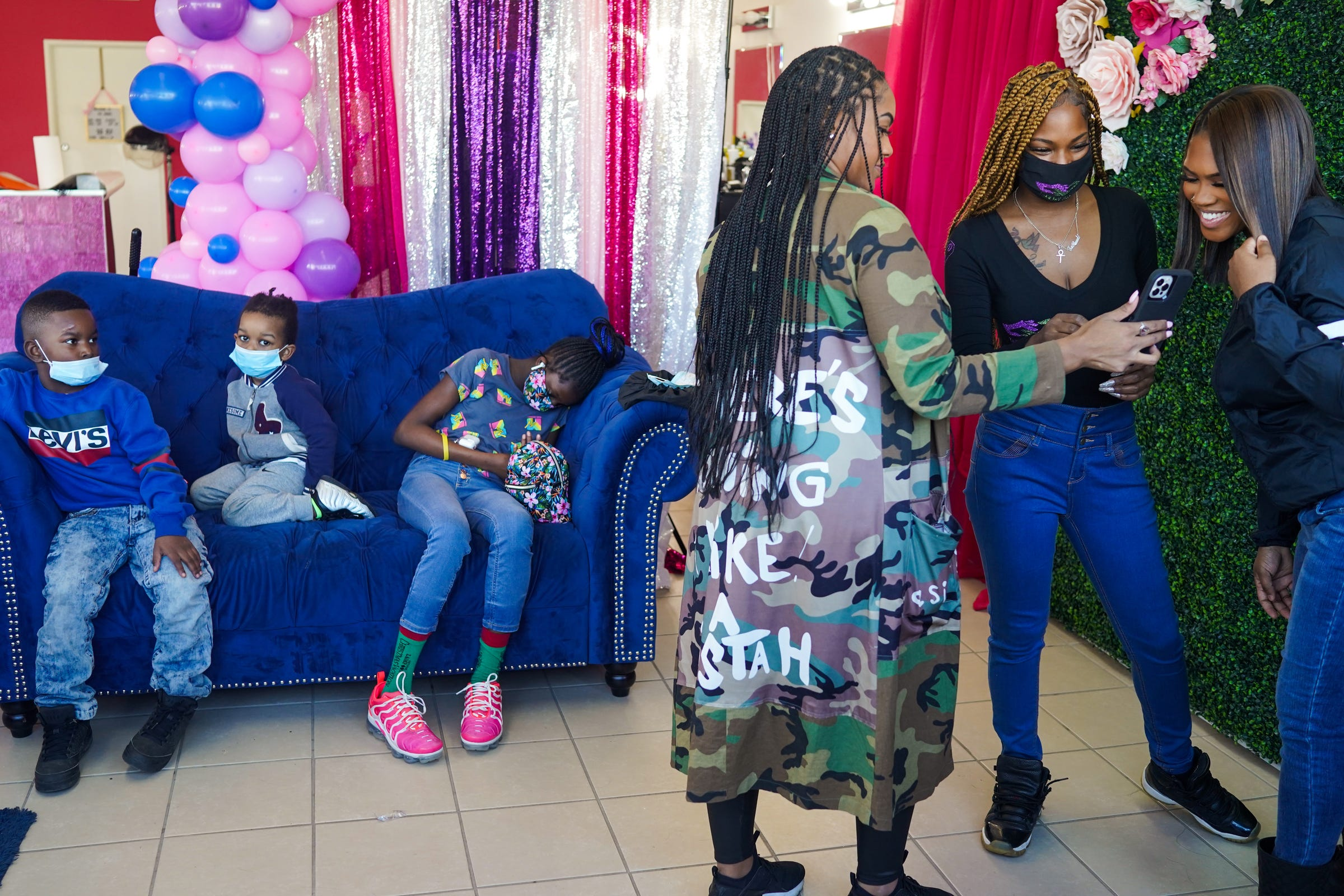 """A'Janae Ruffin, left, and Tia Russell, center, show Aryana Rodgers, right, a picture of herself during the fourth annual Self-Awareness Appreciation Day put on by the non-profit, Take My Hand at the ShayBaby Make Up Bar on Sunday, March 21, 2021, in Warren.  """"I'm grateful for it. It's not often at all that I get to do this,"""" Rodgers said. The event brought together 11 volunteer hairdressers, make-up artists, nail techs and a barber to serve 20 people."""