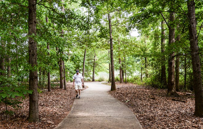 A man walks on a trail at Larry W. Abernathy Waterfront Park in Clemson, across  the street from the proposed Keowee Trail student apartment development.