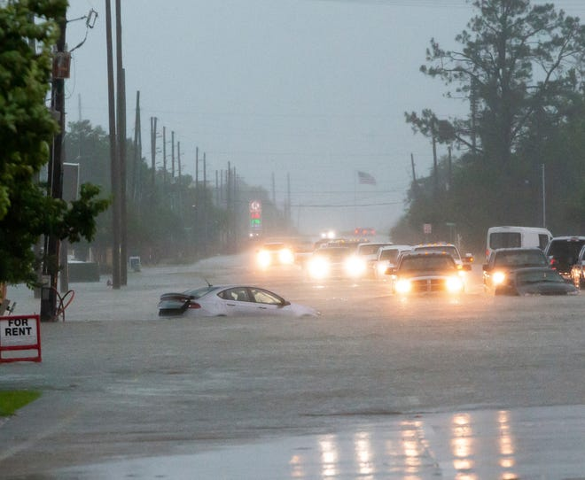 Cars sit stalled on a flooded Nelson Road from heavy rains in Lake Charles, La., Monday, May 17, 2021. (Rick Hickman/American Press via AP)