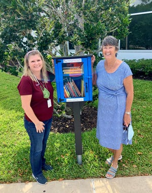 Mackle Park's Samantha Malloy, left, and DAR member Peggy Eckhold present Marco Island's first Little Free Library installed at Mackle Park.