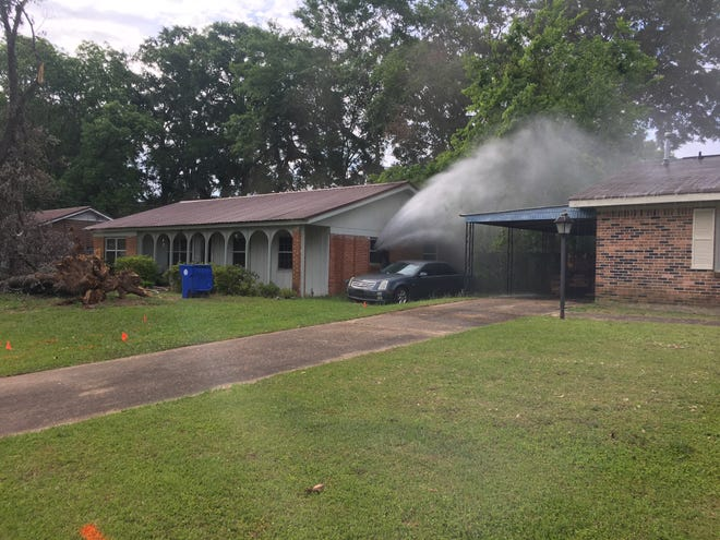 Water sprays from a front bedroom of a house on Guiliford Lane.