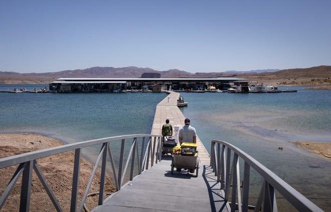 Barbaros Demircar (à droite) et Mike Darin transportent du matériel jusqu'à leur bateau à Temple Bar Marina le 10 mai 2021, dans la zone de loisirs nationale de Lake Mead, en Arizona.