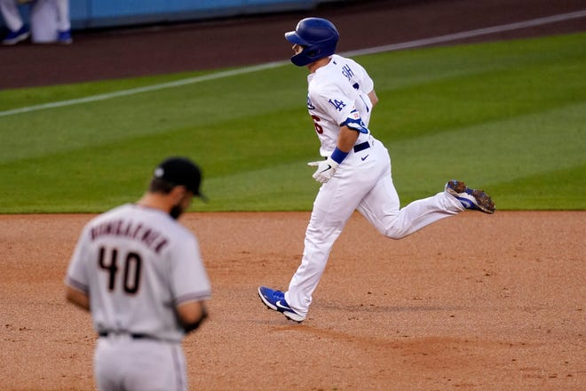 Los Angeles Dodgers' Will Smith, right, heads to third after hitting a solo home run as Arizona Diamondbacks starting pitcher Madison Bumgarner stands on the mound during the second inning of a baseball game Monday, May 17, 2021, in Los Angeles. (AP Photo/Mark J. Terrill)