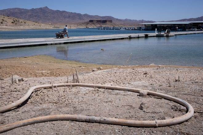 Barbaros Demircar hauls equipment to his boat at Temple Bar Marina on May 10, 2021, in Lake Mead National Recreation Area, Arizona.  The length of the waterline (on the ground) of the marina is adjusted as water levels drop and the marina is moved to deeper water.