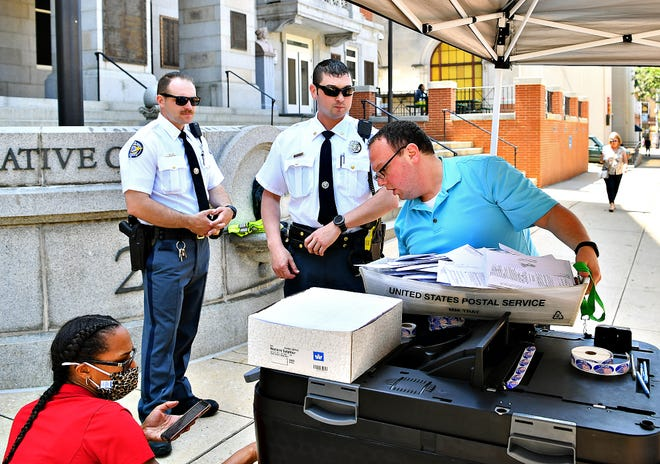 York County Sheriff Deputies Tyler Wilson, center left, and Kurtis Startzel, center right, look on as York County Probation Officer Cathy Gibson, left, assists Bryan Sheaffer, the York County Process and Implementation Coordinator at the York County Elections Office, as he securely collects ballots from the receptacle as residents drop off their mail-in-ballots during the primary election in York City, Tuesday, May 18, 2021. Dawn J. Sagert photo
