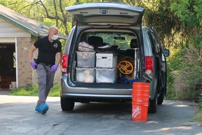 """An Irondequoit police investigator in May organizes tools and evidence collection gear at the home of Christopher Wernle, where police found the body of Edward """"Ted"""" Boucher."""