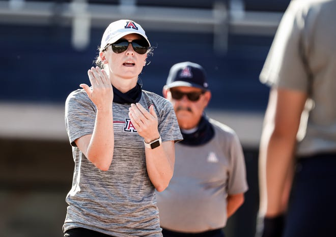 Arizona associate head coach Caitlin Lowe (with head coach Mike Candrea behind) instructs the Wildcats during practice.
