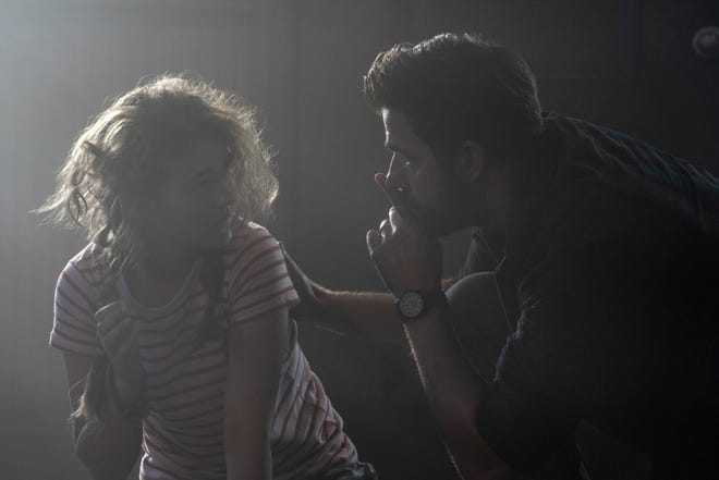 """Regan (Millicent Simmonds) and Lee Abbott (John Krasinski) stay quiet on the first day of an alien invasion in the flashback prologue of """"A Quiet Place Part II."""""""