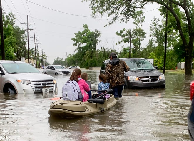 Parents use boats to pick up students from schools after nearly a foot of rain fell in Lake Charles, La., on May 17, 2021.