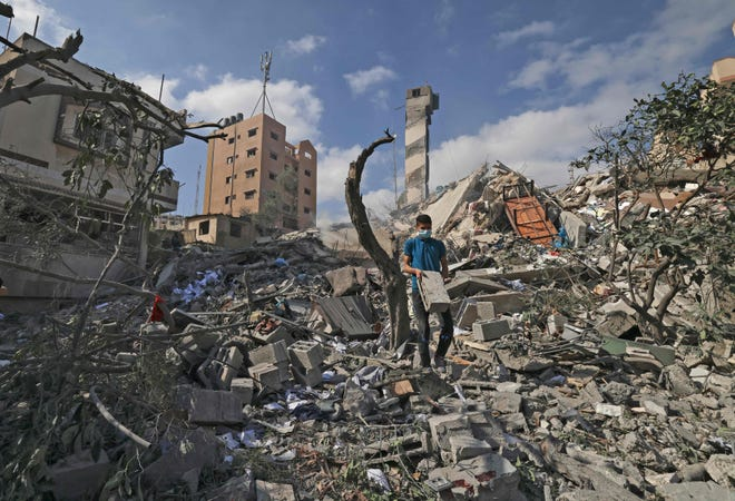 A Palestinian youth looks for salvageable items amid the rubble of the Kuhail building which was destroyed in an early morning Israeli airstrike on Gaza City on May 18, 2021. The building had a printshop and university accessories and books storage facility for educational institutes in Gaza as well as a mosque.