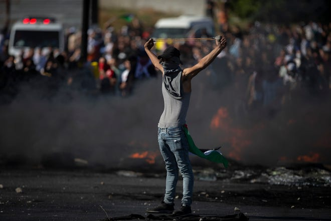 Palestinians clash with Israeli forces at the Hawara checkpoint, south of the West Bank city of Nablus, Tuesday, May 18, 2021.