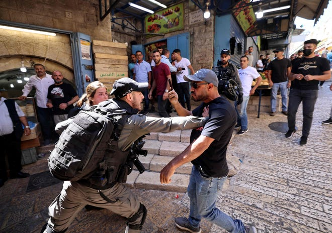 An Israeli border police officer confronts a Palestinian man during protests in east Jerusalem on May 18, 2021.