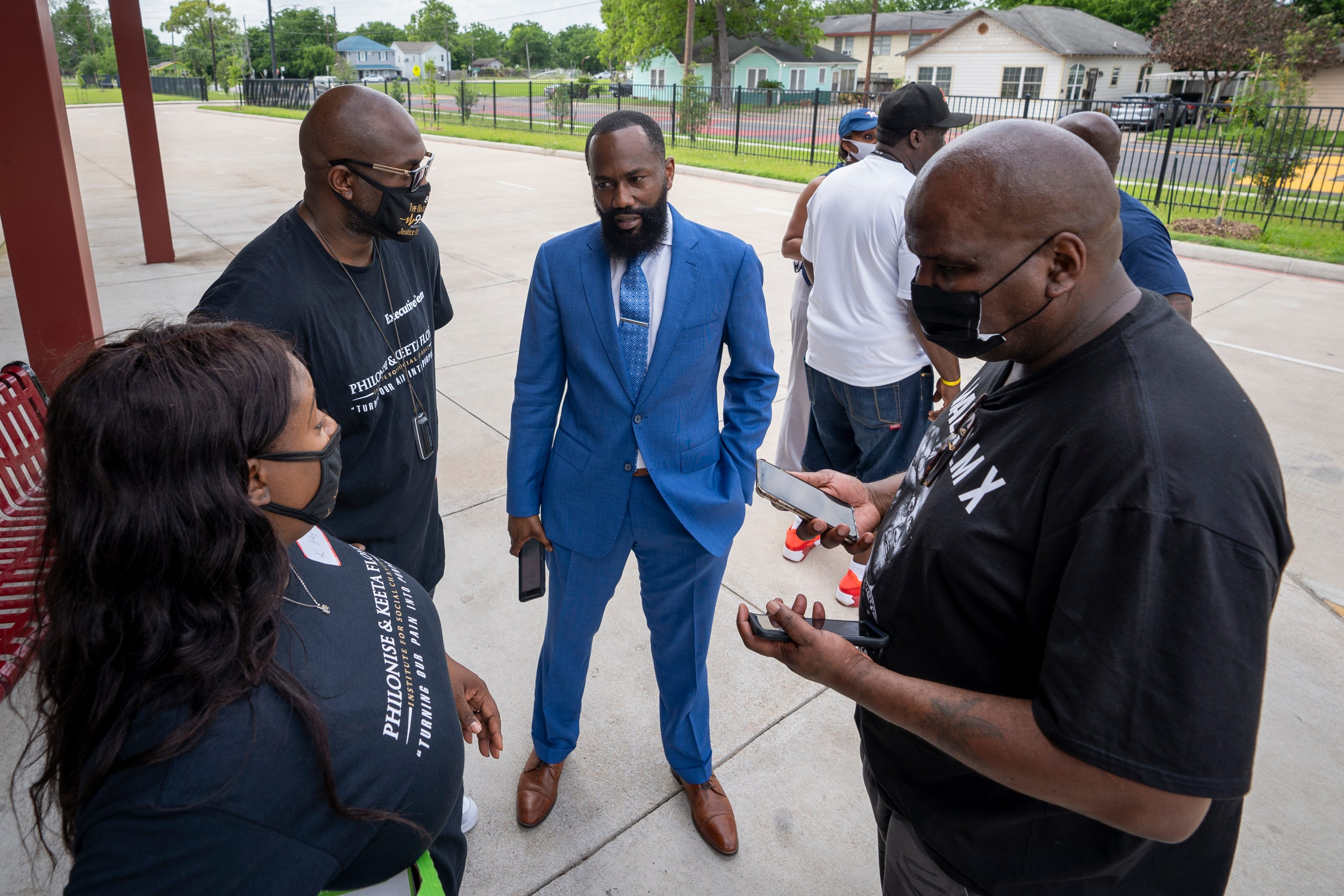 Chris Johnson (center) of Good Hope Missionary Baptist Church speaks with members of George Floyd's family outside Jack Yates High School in the Third Ward of Houston, Texas.