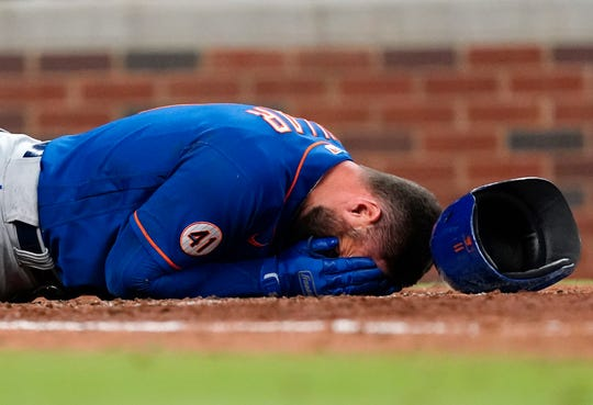Kevin Pilar of the New York Mets is lying on the ground after being hit in the face with the pitch by Atlanta Braves pitcher Jacob Webb in the seventh inning.