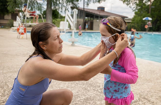 Amanda Davidson helps her daughter, Lyle, put on her face mask after they got out of the pool at Rosewood Pool last June. Kids and unvaccinated people still need to wear masks in crowded spaces outdoors and indoors.