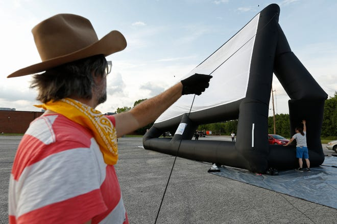 Ciné board member Todd Kelly and employees from Ciné raise the theater's inflatable drive-in movie screen in the parking lot of the former General Time/Westclox clock factory on Newton Bridge Road in Athens, Ga., on Tuesday, May 18, 2021. The day was a test run.