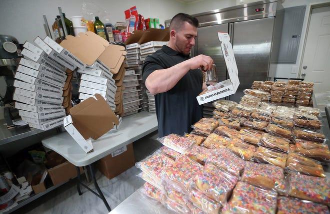Zachary Buckeye, owner of Buckeye Brownies, fills orders in his home bakery, Monday, May 17, 2021, in Akron, Ohio. [Jeff Lange/Beacon Journal]