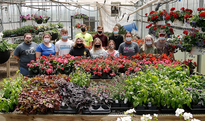Hillsdale FFA greenhouse management class members, from left, Kayedeance Scott, Megan Schwendeman, Caden Fickes, Grace Glass, Hudson Heller, Zoey McBride, Zach Shoudt, Lilly Bolen, Kyle Hower, Olivia Traylor, Hayley Marcum and Garett Wickham pose in the greenhouse Wednesday with the plants they have grown that will be on sale Thursday, Friday and Saturday.