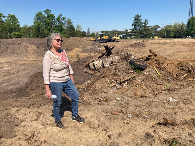 """Jeanne Brown stands on the construction site where a Wawa will open this year, directly across from her home. """"Eight gas pumps. How am I supposed to back out of my driveway?"""" she said."""
