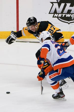 Pittsburgh Penguins' Sidney Crosby (87) and New York Islanders' Oliver Wahlstrom (26) chase down the puck during the third period of an NHL hockey game,  Feb. 20, 2021, in Pittsburgh. (AP Photo/Keith Srakocic)