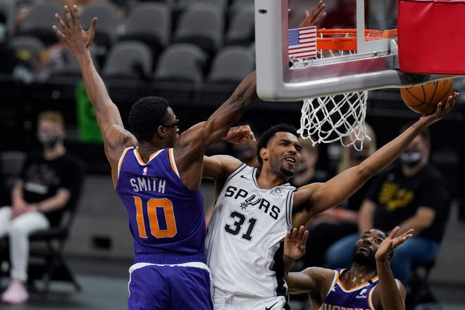 San Antonio Spurs forward Keita Bates-Diop (31) drives to the basket past Phoenix Suns forward Jalen Smith (10) during the second half of an NBA basketball game in San Antonio, Saturday, May 15, 2021.