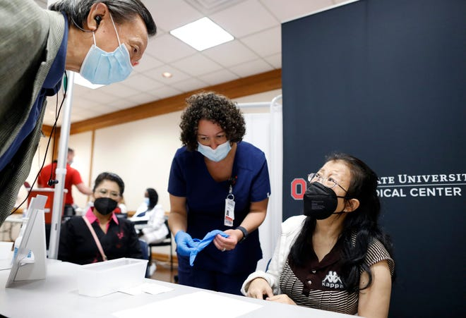 Translator Sumit Gunanukorn, left, ask questions of Ketsana Khamsombath, right, for registered nurse Heather Less before giving Khamsombath her second COVID-19 vaccination at Ohio State East Hospital on May 19.