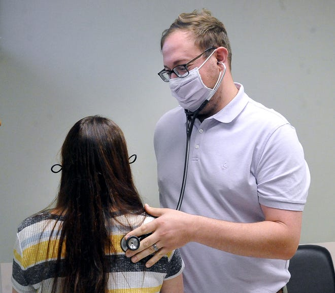 Dr. John Prokopdo listens to a patient's lungs.