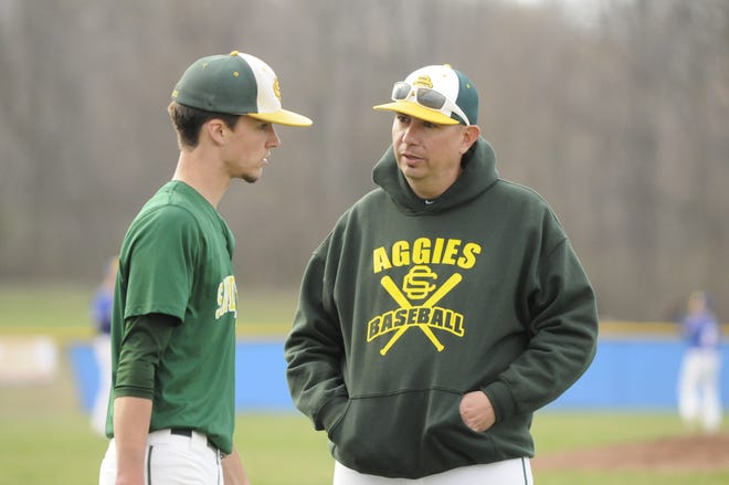 Sand Creek baseball coach Wayne Perry, right, talks to Griffin Reynard during a TCC doubleheader at Madison on April 17, 2019. Perry has been named the new girls basketball coach at Sand Creek, taking over for Matt Benge.